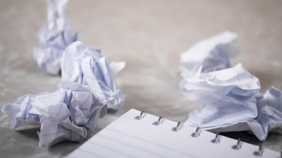 Portfolio image - crumpled up pieces of paper surrounding a notebook