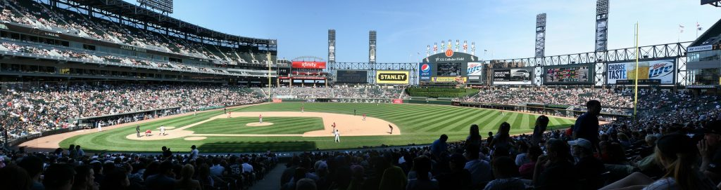 Wide view of a baseball stadium with stands full of brave people risking total boredom