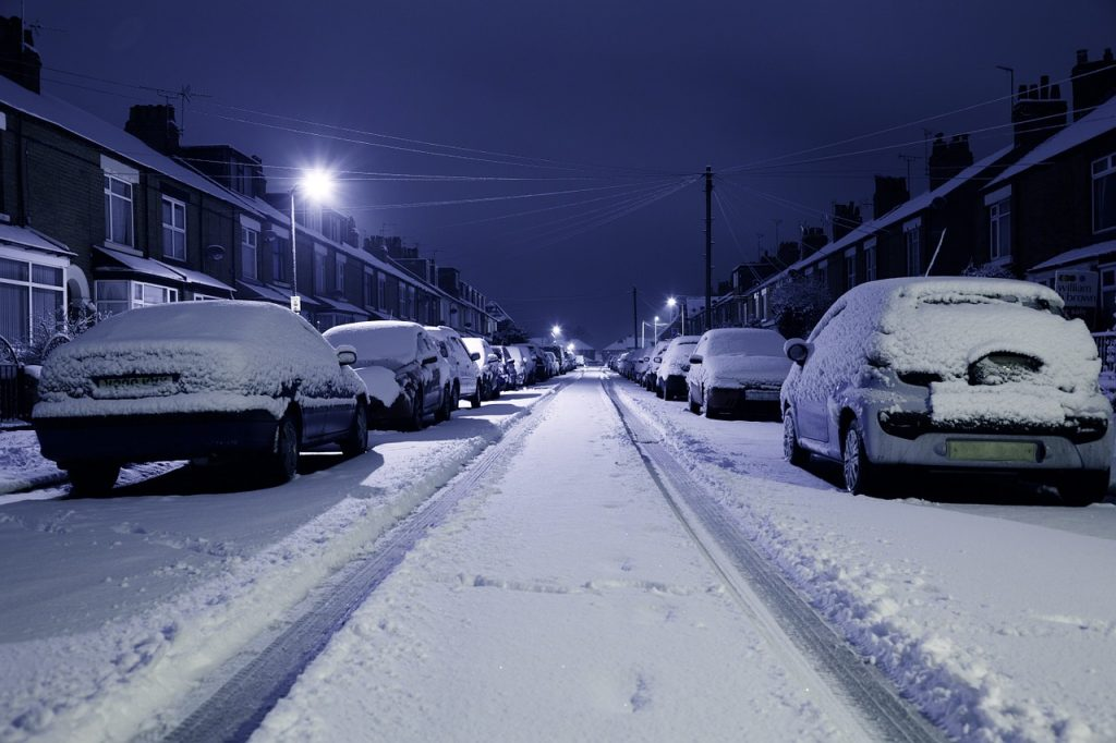 A snow covered street at night, rows of cars on both sides