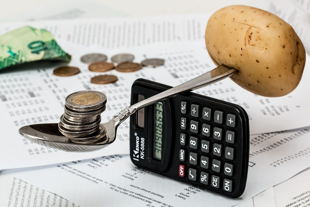 Calculator balanced on one edge. On top is a spoon, carefully balanced with a potato stuck on the handle end and a stack of coins stacked in the bowl.
