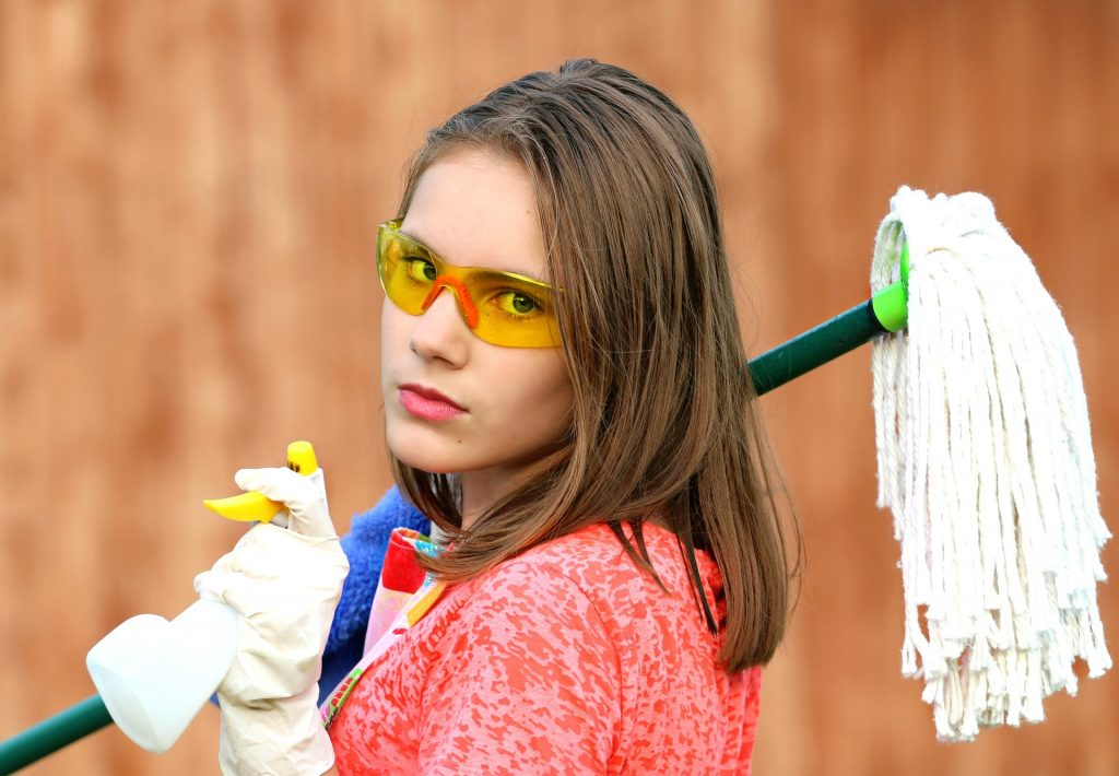 Young woman with an assortment of cleaning supplies and a look of utter disdain and boredom on her face
