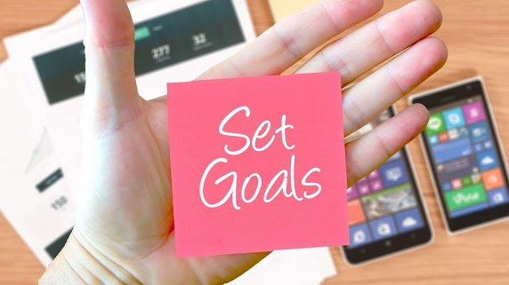 "Portfolio image - a sticky note being held in a hand. the sticky note says ""Set goals."""