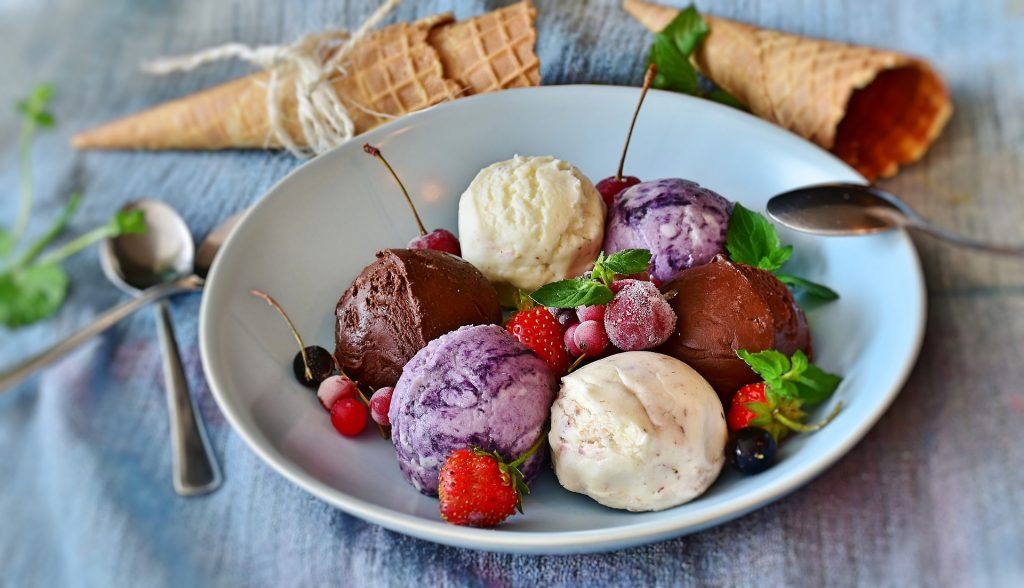 A large bowl with six scoops of ice cream - two each of three flavors. Mixed berries and mint leaves are scattered around. There are three spoons and three waffle cones to eat the ice cream with.
