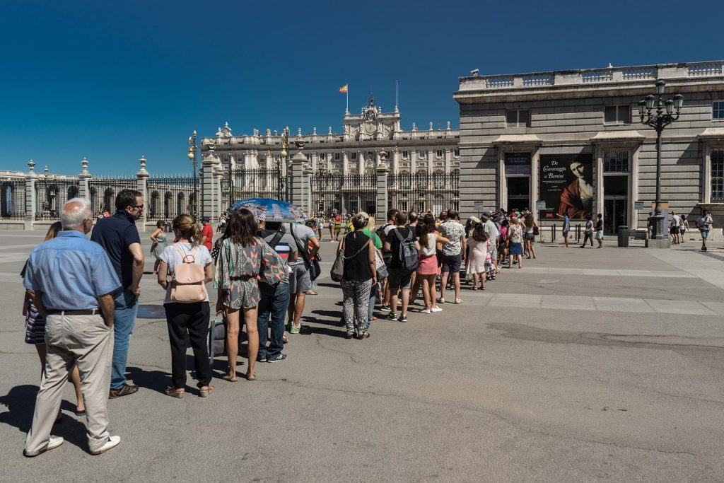 Long line of people waiting to enter a stone building