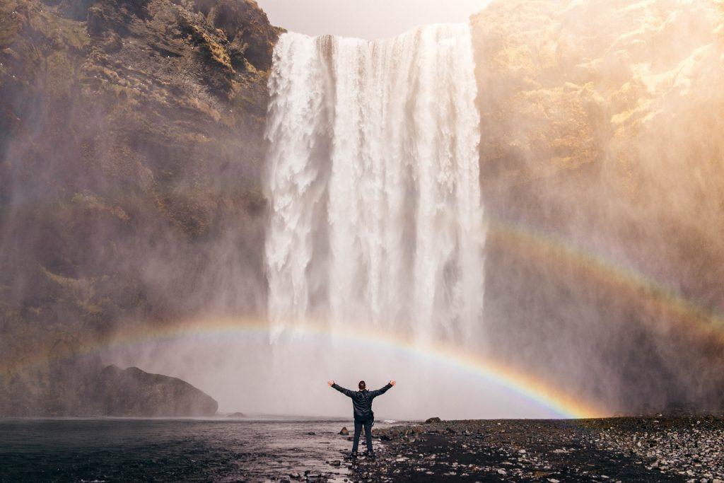 A person standing , legs shoulder width apart, arms upraised, in front of a giant waterfall that's creating a rainbow at the bottom