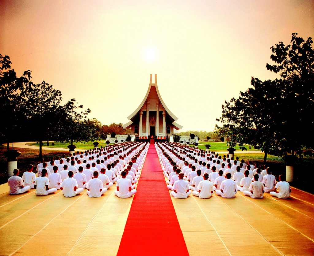 hundreds of monks in rows in front of a Buddhist temple