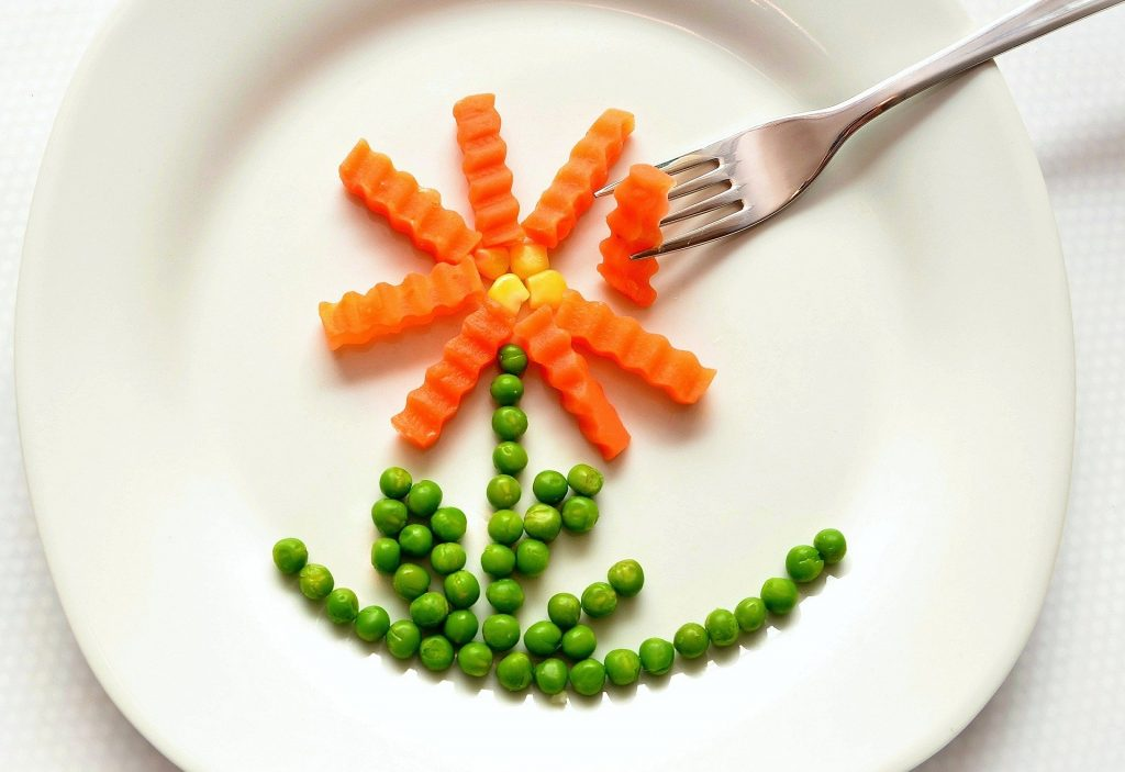 A round white plate on which carrot slices, corn kernels, and peas have been arranged to form a flower. A silver fork is picking up a piece of carrot.