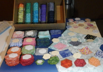 A small table covered with a rainbow-colored cornucopia of quilt pieces and supplies, including several hundred hand-stitched hexagons ready to be sewn together